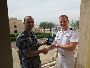Major Hisham Al-Faragh, Royal Jordanian Naval Force, presents a plaque to CTF150 Director Plans and Exercises CDR Trevor Maclean, Royal Canadian Navy.