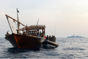 HMS Monmouth's Blue Team conducts Approach and Assist operations with local fishing dhows as the ship keeps watch in the distance
