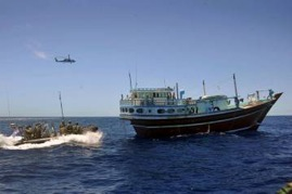 HMAS Toowoomba's boarding party, supported by their Sea Hawk helicopter, approaches a dhow for boarding.
