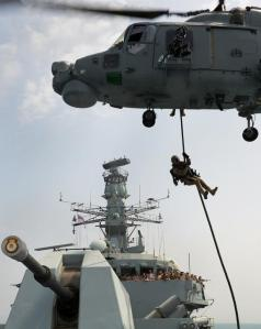 HMS Monmouth's Royal Marines Boarding Team rapid rope from the ship's Lynx Mk 8 Black Knight onto the Foc'sle as part of a boarding display as Kuwaiti Staff College students look on from the bridge.