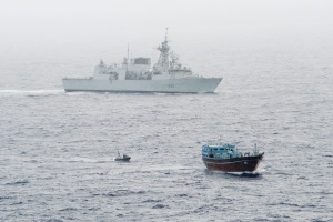 HMCS Toronto watches over the suspect dhow as her boarding team makes its approach