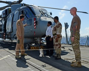 Colonel Ali Saleen of the Yemen Navy and Lieutenant Colonel Saalih Muhamed Alhumaymi of the Yemen Marines being shown around HMS Kent's Merlin helicopter