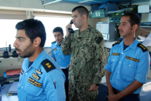 Lt Dennelly of the US Coast Guard and members of the Kuwait Naval Force on the bridge of the Kuwaiti warship Al Fahaheel