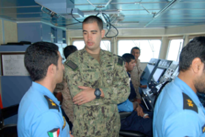 Lt Dennelly of the US Coast Guard and members of the Kuwait  Naval Force and Kuwait Coast Guard on the bridge of the Kuwaiti warship Al Fahaheel