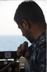 Radio communications are vital during Search and Rescue missions. Here, a member of RBNS Al Jaberi's crew coordinates the search for the simulated casualty.