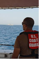 A US Coast Guard sailor looks out at RBNS Al Jaberi