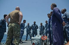 US Navy Lieutenant Cliff Oversby talks with sailors aboard RBNS Al Jaberi