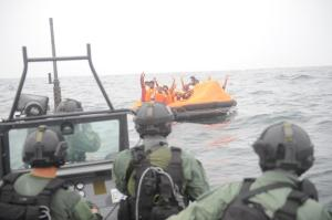 Pure Relief: The stranded sailors wave and cheer as ROKS Wang Geon's seaboat approaches.