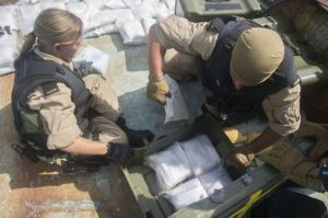 Members of HMCS Toronto's boarding team gather together the illegal narcotics. Photographed by Leading Seaman Dan Bard, Canadian Navy