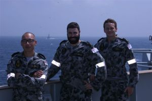 Left to right Able Seaman Luke Luong, Brendan McPherson and Cory Pickett with HMAS Melbourne in the back ground