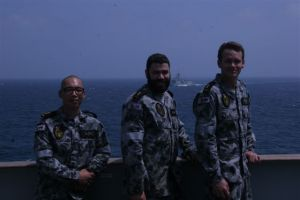 Left to right Seaman Luke Luong, Brendan McPherson and Cory Pickett with HMAS Melbourne in the back ground