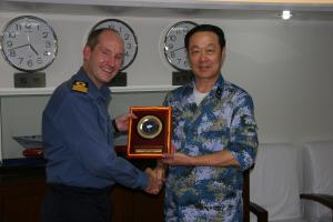 Commodore Jeremy Blunden, Royal Navy, Commander Combined Task Force 151 receives a plaque from Rear Admiral Jiang Zhonghua, People's Liberation Army (Navy), Commander Chinese Escort Task Group.