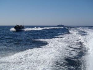 HMS Montrose's Boarding Teams speed away from the ship to visit dhows