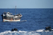 HMAS Darwin's ridged hull inflatable boats, with members of the boarding party team embarked, approach the suspicious dhow to conduct a boarding.
