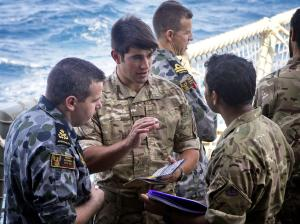Boarding party members from HMAS Darwin engage with members of during a meeting at sea.