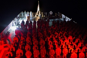 HMAS Darwin ships company form up on the flight deck to commemorate ANZAC Day during a dawn service in the middle of the Indian Ocean.