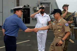 Commander Phil Nash greets Captain Kim Jeong-Hyun during a fuel stop in Salalah.