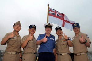 Commander Phil Nash, Commanding Officer of HMS Defender enjoys a moment with Captain Kim Jeong-Hyun (2nd in from right) and his ship's company during a visit to Salalah, Oman.