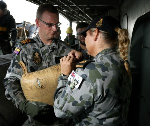 The Executive Officer of HMAS Toowoomba presents a 20kg bag of hashish for accounting and tagging to the Naval Police.