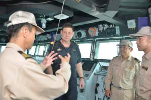 Commodore Tony Millar being briefed on the capability updates on the bridge of JS Takanami by Captain Tsutomu Okawa