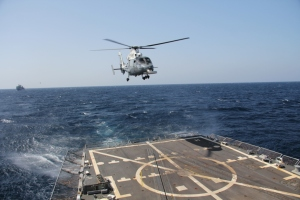 Royal Saudi Naval Force Ship HMS Yanbu's helicopter making approach over the flight deck of USS Dewey during Focused Operation Taawun al Behr.