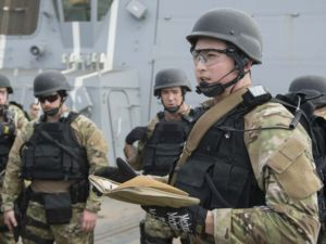 The boarding team from USS Dewey prepares to board a dhow in the Middle East