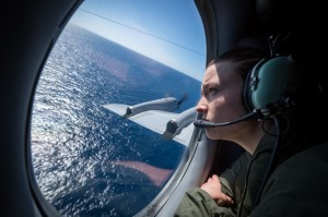 An Air Warfare Specialist scans the ocean from an observation window on the P-3K2 Orion during a routine maritime patrol
