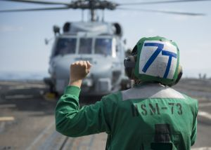 Aviation Electrician's Mate Airman Jamie Badgett, assigned to the Battle Cats of Helicopter Maritime Strike Squadron 73, performs landing signalman duties on the flight deck of USS Dewey