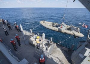 Sailors lower a rigid-hull inflatable boat from the destroyer USS Dewey during boarding operations.