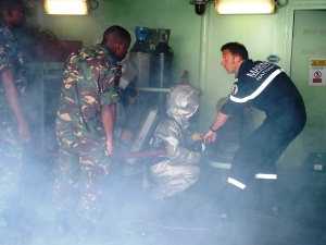 French officer from FS Var describing French fire alarm security processes to Tanzanian seamen during a security training (SECUREX), onboard the ship