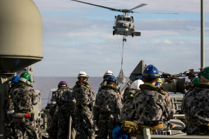 Crew members from HMAS Newcastle during a replenishment at sea with FS Var, and vertical replenishment (VERTREP) with Newcastle's Seahawk helicopter.