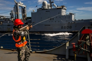 Crew member from HMAS Newcastle using a line-throwing gun during a replenishment at sea with FS Var.