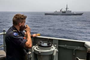 Sub Lieutenant Sam Mason, on exchange from the Royal New Zealand Navy, gives conning orders to the helmsman as HMAS Newcastle maintains station with the French Frigate, FS Sarcouf, as part of a crew exchange visit between the two ships in the Gulf of Oman. HMAS Newcastle is tasked to carry out maritime security patrols in the Indian Ocean in support of Operation MANITOU. *** Local Caption *** HMAS Newcastle is deployed in the Middle East Region on Operation MANITOU, Australia's contribution to the US-led Combined Maritime Forces (CMF). The CMF undertakes patrols in the broader northwest Indian Ocean to both combat piracy and to intercept the trafficking of drugs that help fund international terrorism. The CMF also encourages regional cooperation to create a safer maritime environment. HMAS Newcastle is on her fifth deployment to the Middle East Region as is the 60th rotation of a RAN vessel since the first Gulf War in 1990.
