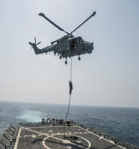 Royal Marine fast roping to the deck of USS McFaul