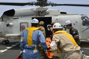 Caption: The patient is loaded onto the Japanese helicopter onboard Korean ship ROKS Chungmugong Yi Sun-sin before transfer to Djibouti.