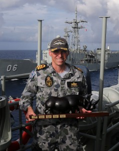 Commander Bill Waters, Commanding Officer HMAS Melbourne, is seen 'Taking the Weight' as Melbourne assumes responsibilities from HMAS Newcastle (rear of photo)for Operation MANITOU in the Middle East Region. 'Taking the Weight' is a Navy tradition that symbolises the transfer of the prestige, privilege and burden of command. In this case the weight has taken the form of a rhinoceros.