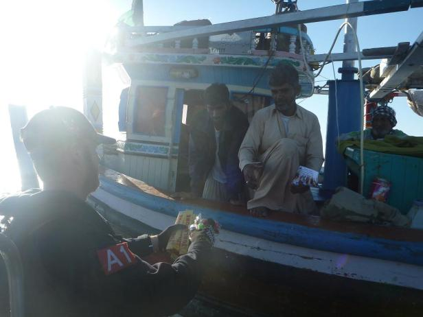 2. Royal Australian Navy personnel handout information and chocolates while patrolling the Makran Coast