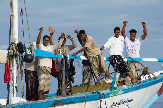 17. The crew of a fishing dhow in the Gulf of Aden farewell USN personnel