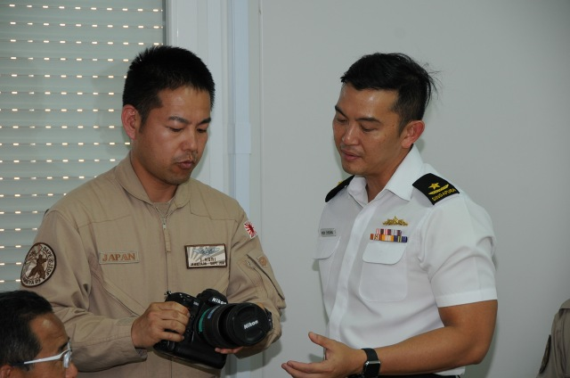 CCTF 151 RADM Ken Cheong gets a brief from the DAPE photographer whose photographs provide citical information to counter-piracy operations