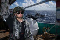 Able Seaman Electronic Warfare Liam Salminen stands as a sentry during the search of a dhow while on patrol in the Middle East Region.