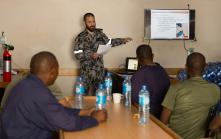 Leading Seaman Marine Technician Aaron Jones delivers a lesson in basic marine outboard motor maintenance to members of the Tanzanian Transnational Organised Crime Unit in HMAS Arunta while alongside in Dar Es Salaam, Tanzania.